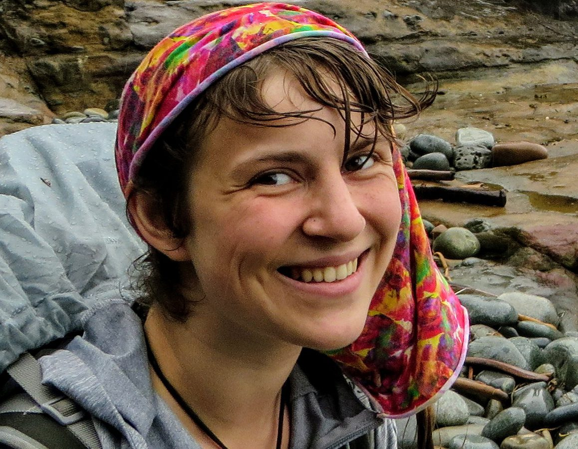 A happy young female hiker smiling and soaking wet standing on the rocky shore along the West Coast Trail, on Vancouver Island, British Columbia, Canada